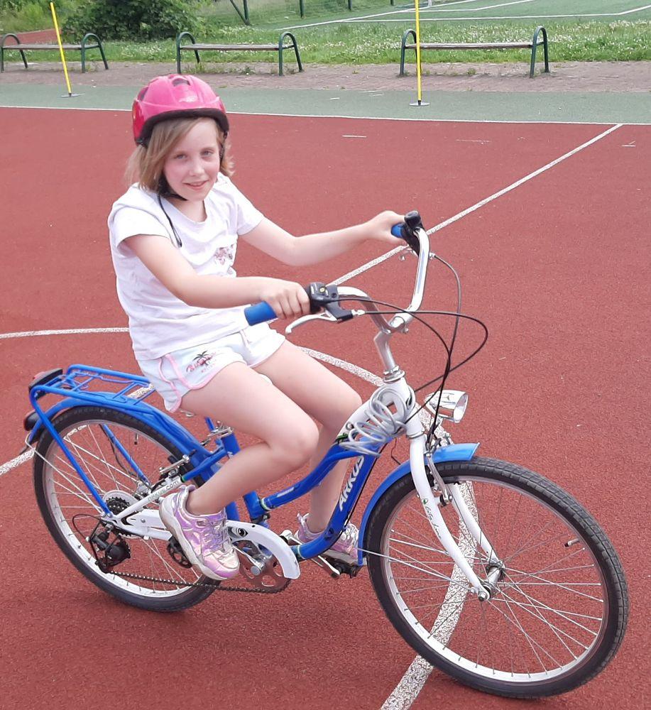 Alicja na niebieskim rowerze w kasku.